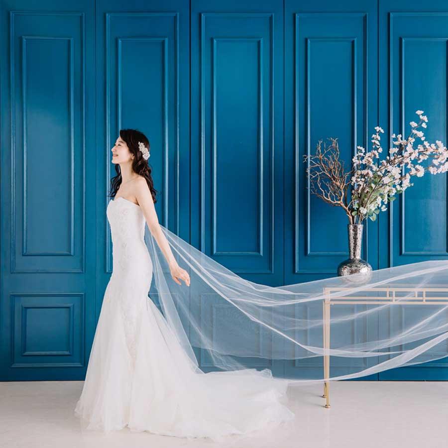 青い壁面、ベールがたなびく、スレンダーなウェディングドレス
